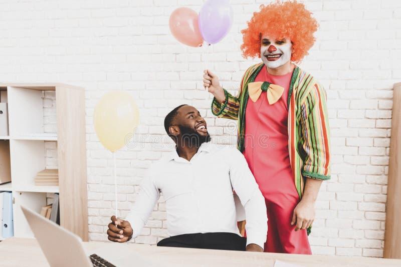 Ung man i clownen Costume med Baloons i regeringsställning royaltyfria foton