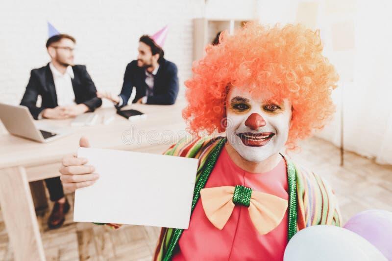 Ung man i clownen Costume på möte i regeringsställning royaltyfri bild