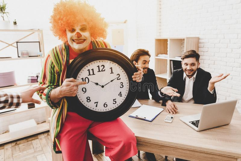 Ung man i clownen Costume på möte i regeringsställning arkivbild