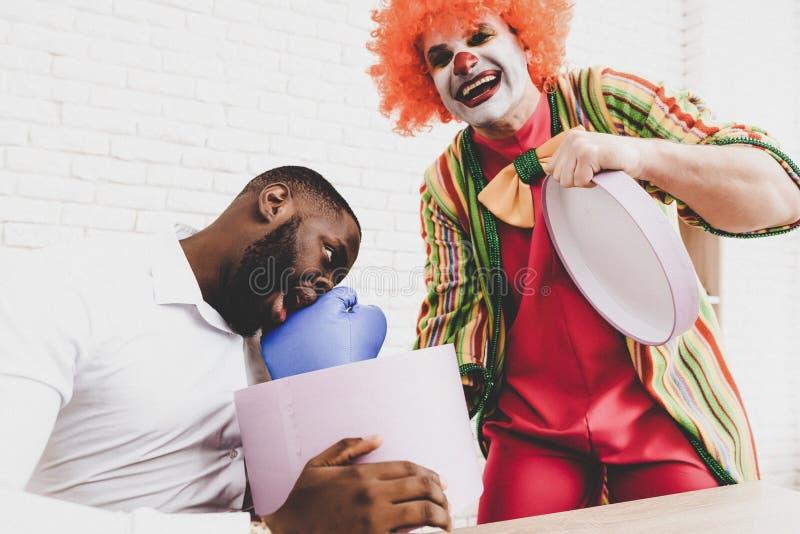 Ung man i clownen Costume på möte i regeringsställning royaltyfria bilder