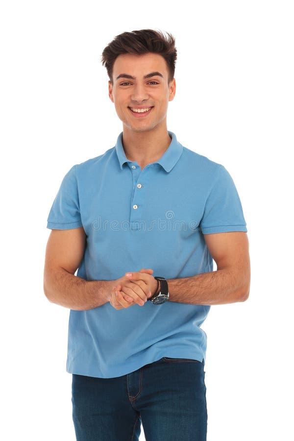 Ung man i den blåa skjortan som trycker på händer arkivfoto