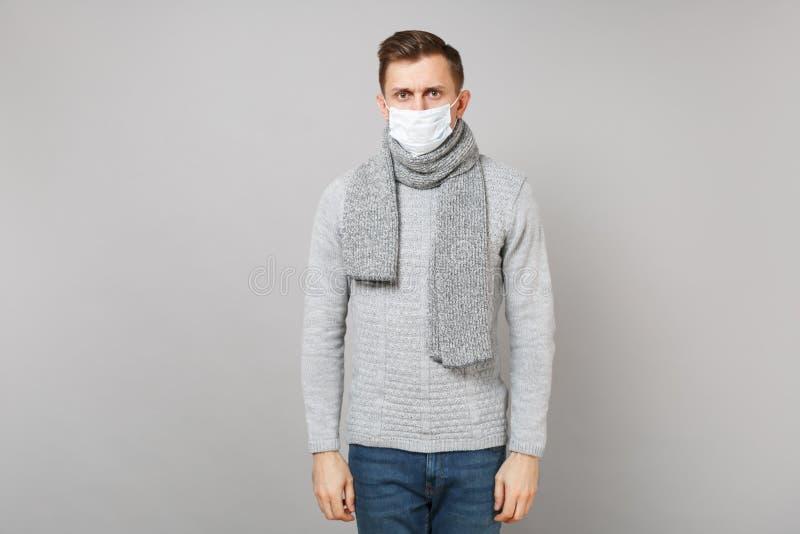Ung man i den gråa tröjan, halsduk med sterilt anseende för framsidamaskering som isoleras på grå bakgrund, studiostående Sunt royaltyfria foton