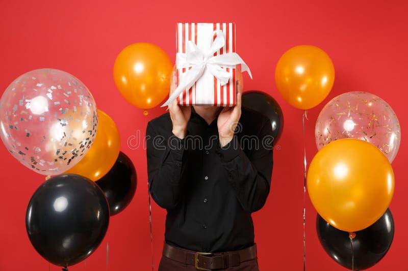 Ung man i den svarta klassiska skjortan som täcker framsidan med den röda asken med gåvan som är närvarande på ljusa röda bakgrun arkivbilder