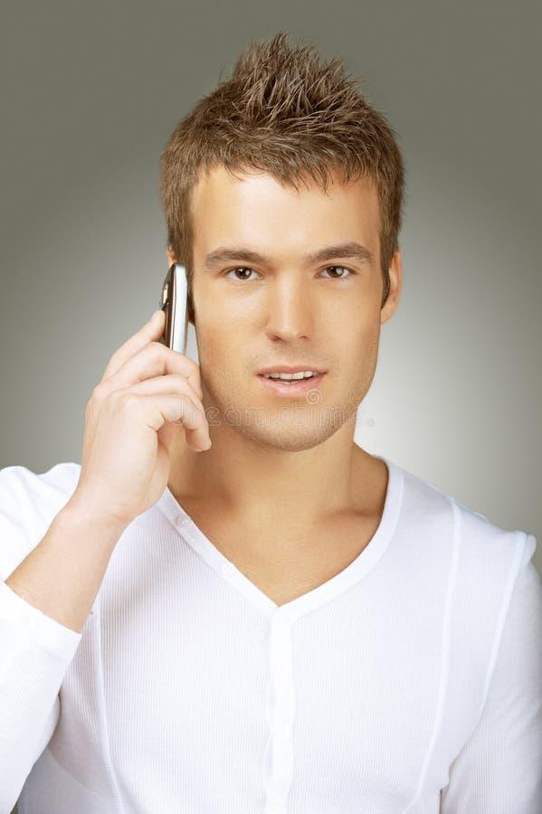 Ung man i den vita skjortan som talar på mobiltelefonen arkivfoton
