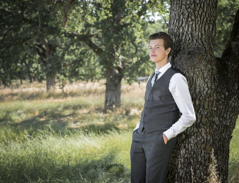 Ung man i dräkt och band som lutar utomhus mot träd royaltyfri bild