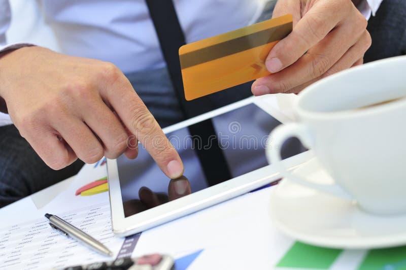 Ung man i dräkt som direktanslutet shoppar via en minnestavladator royaltyfria bilder