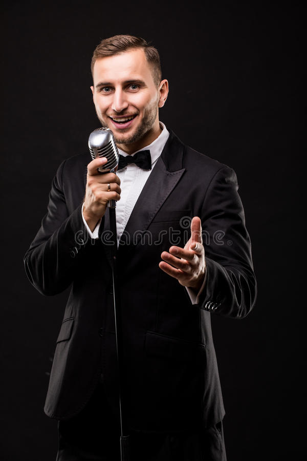 Ung man i dräkt som sjunger över mikrofonen med energi arkivfoto