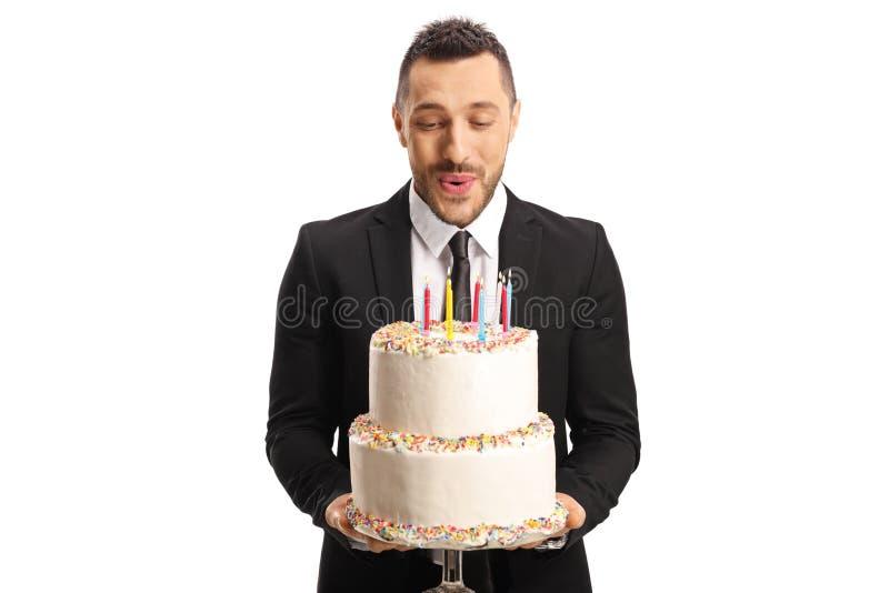 Ung man i en dräkt som rymmer en födelsedagkaka och blåser stearinljus arkivbilder