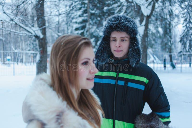 Ung man i en pälshatt med en earflap och en flicka i ett beige pälslag mot bakgrunden av vinterskogen royaltyfria foton
