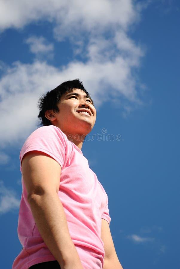 Ung man i en rosa skjorta mot den blåa skyen arkivbild