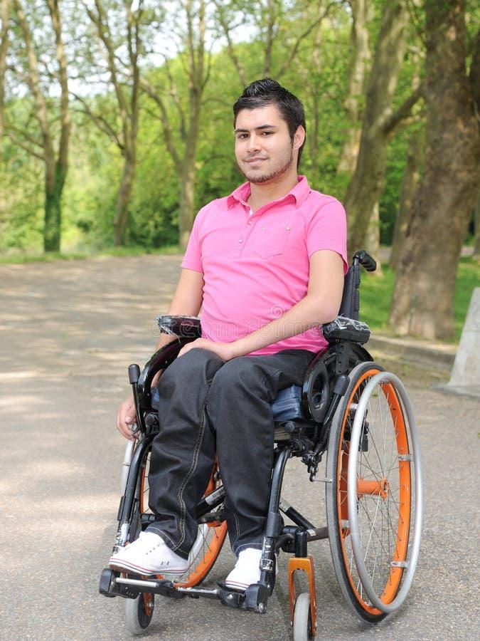 Ung man i en rullstol royaltyfri foto