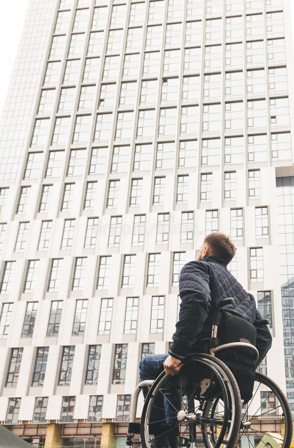 Ung man i en rullstol mot bakgrunden av ett modernt höghus arkivfoton