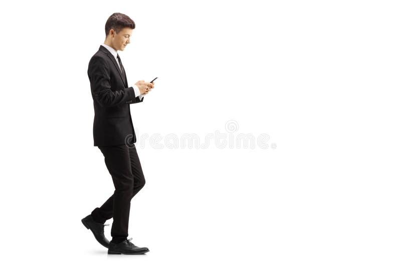 Ung man i en svart dräkt som går och skriver på en mobiltelefon royaltyfri bild