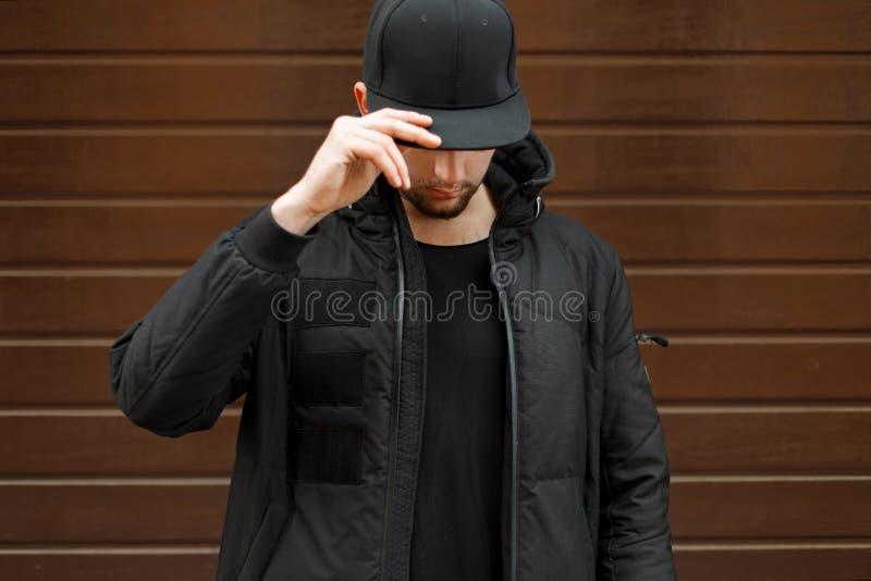 Ung man i en svart trendig baseballmössa royaltyfria bilder