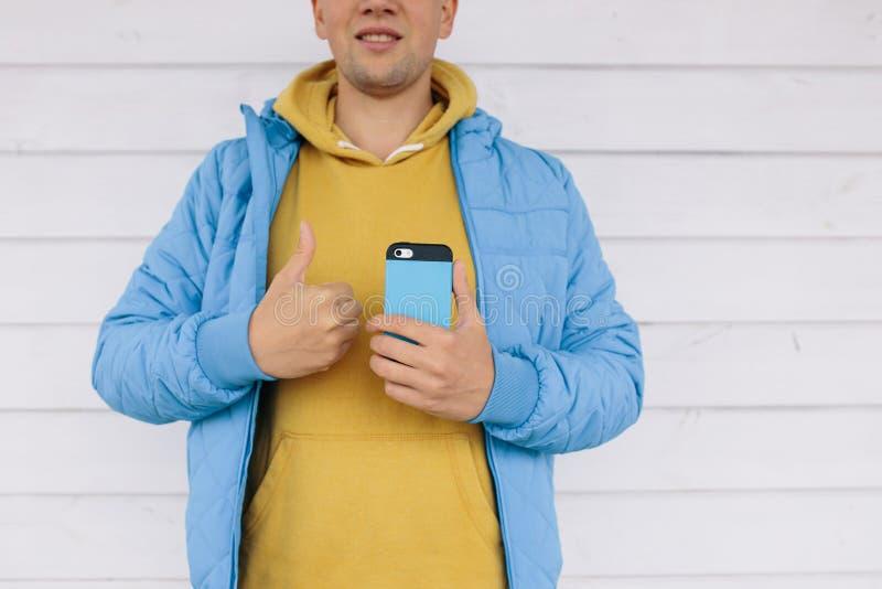 Ung man i ett blått omslag som rymmer upp en mobiltelefon i en hand och annan uppvisning tummar arkivfoto