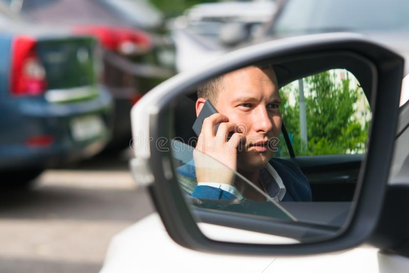 Ung man i ett omslag som talar på telefonen, reflexion i spegeln av en bil royaltyfri bild