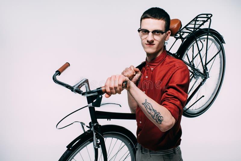 Ung man i exponeringsglas som rymmer hans cykel på skuldra royaltyfri fotografi