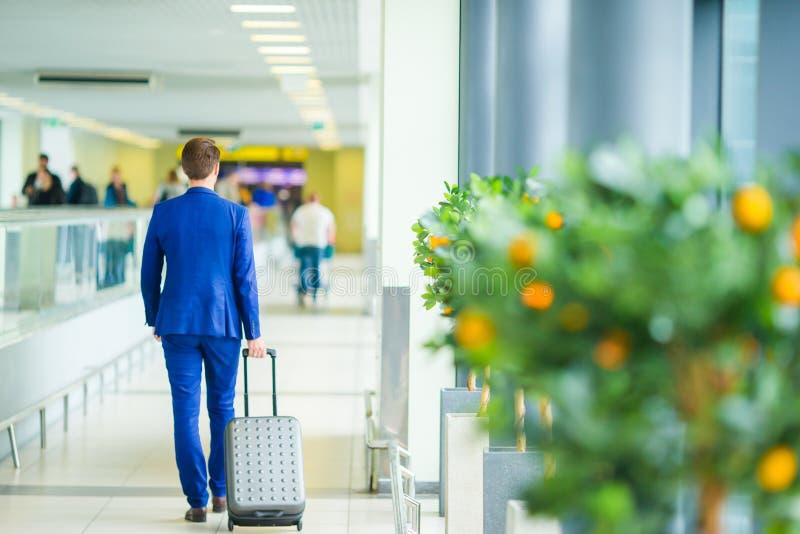Ung man i flygplats Bärande dräktomslag för tillfällig ung pojke Caucasian man med mobiltelefonen på flygplatsen, medan vänta arkivbild