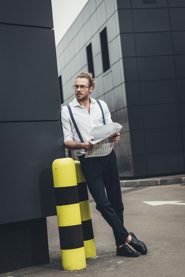 Ung man i glasögon som rymmer tidningen, medan luta på kontorsbyggnad arkivbilder