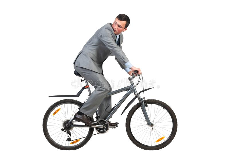 Ung man i grå kostym på cykel fotografering för bildbyråer