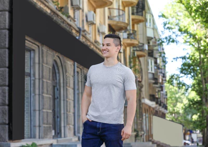 Ung man i grå t-skjorta utomhus arkivfoto