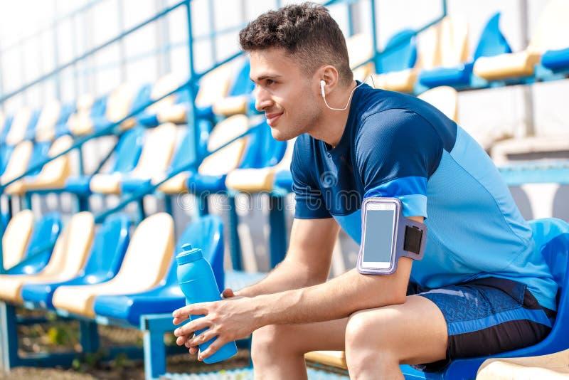 Ung man i hörlurar på stadion utanför att sitta med armbindeln för smartphone med flaskan av lyssnande musik för vatten fotografering för bildbyråer