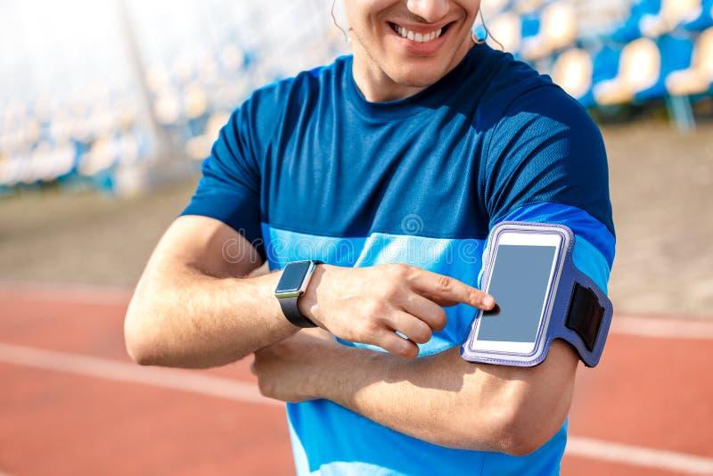 Ung man i hörlurar på stadion utanför att stå med armbindeln för sången för tryckande på skärm för smartphone den gladlynta ändra arkivfoton