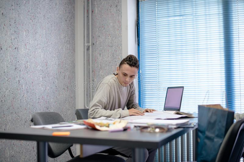 Ung man i hans idérika kontor royaltyfri bild