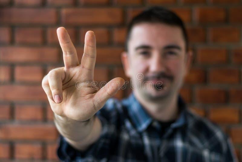 Ung man i hans 30-tal som visar tre fingrar Selektivt fokusera royaltyfria bilder