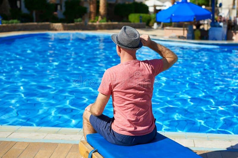 Ung man i hatten som sitter på en soldagdrivare nära simbassängen, begreppstid att resa Koppla av i pölsommaren arkivbild