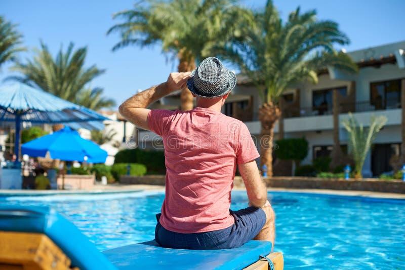 Ung man i hatten som sitter på en soldagdrivare nära simbassängen, begreppstid att resa Koppla av i pölsommaren i Egypten arkivbilder
