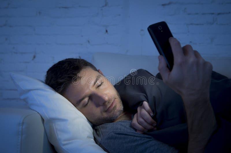 Ung man i hemmastatt falla för sängsoffa sovande sent på natten, medan genom att använda mobiltelefonen i lågt ljus arkivbilder