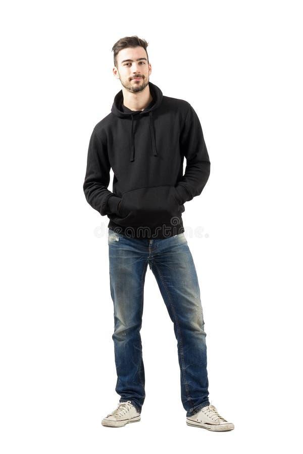 Ung man i hoodie med händer i fack som ler på kameran royaltyfria foton