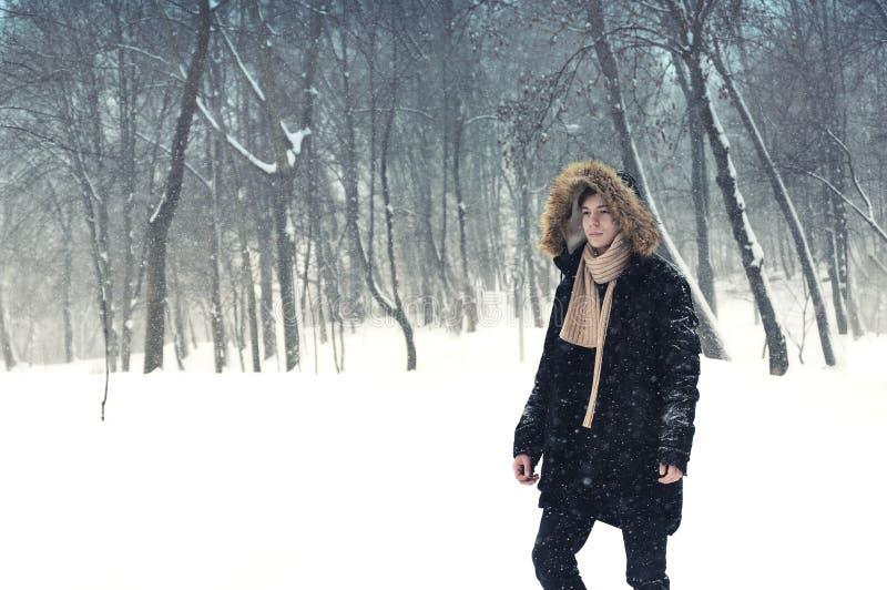 Ung man i huv i parkera i vinter arkivfoto