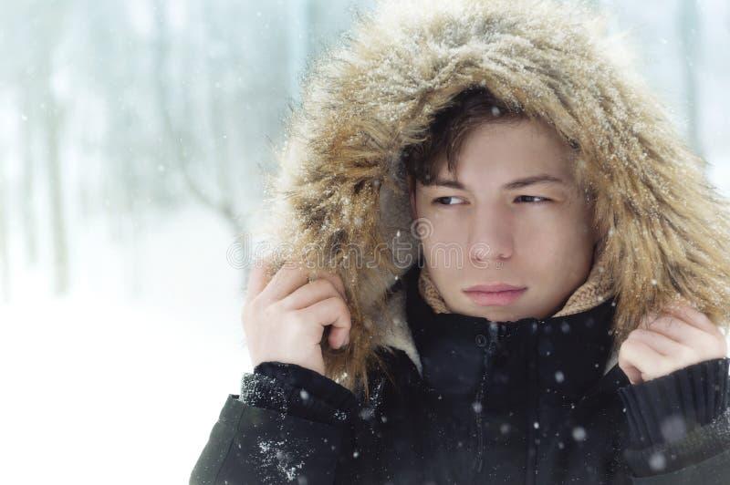 Ung man i huv i parkera i vinter royaltyfri bild