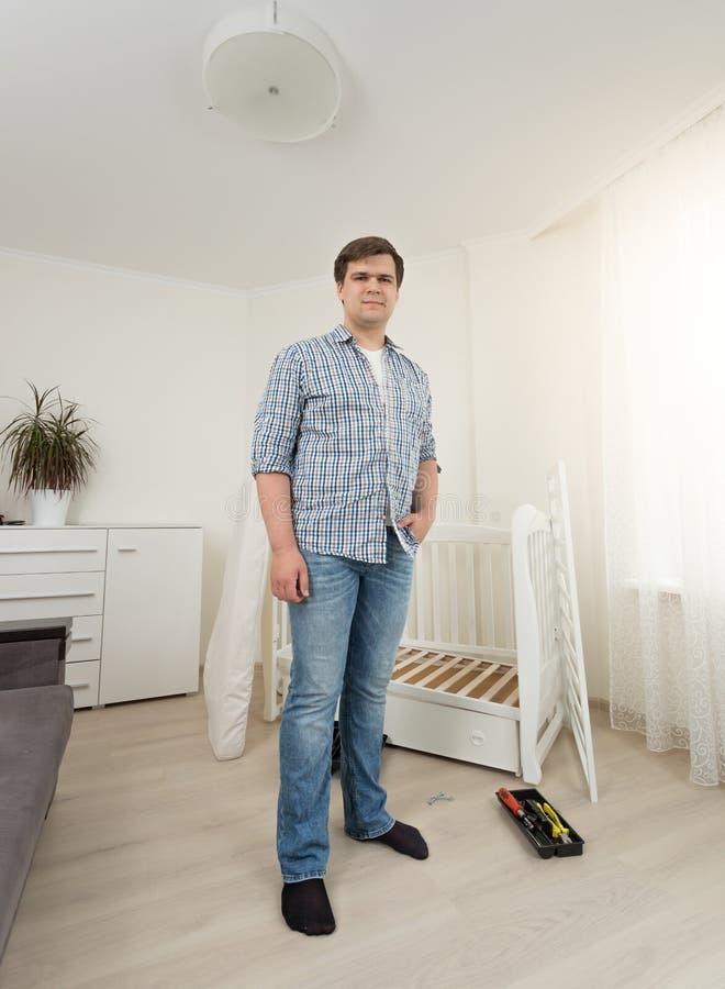 Ung man i jeans som poserar i sovrum med demontert möblemang fotografering för bildbyråer
