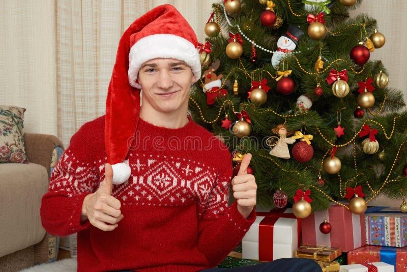 Ung man i julgarnering Hemmiljö med gåvor och granträdet Feriebegrepp för nytt år royaltyfri bild