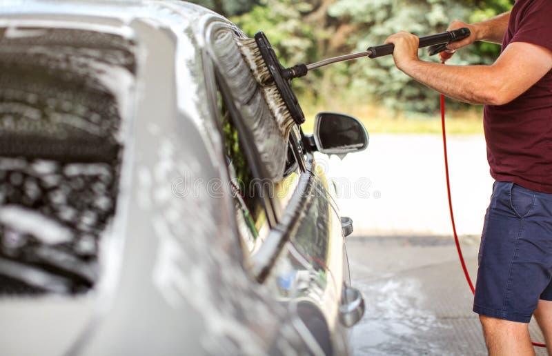 Ung man i kortslutningar och t-skjorta som tvättar hans bil i självservecarwashen, rengörande sidofönster med borsten arkivfoton