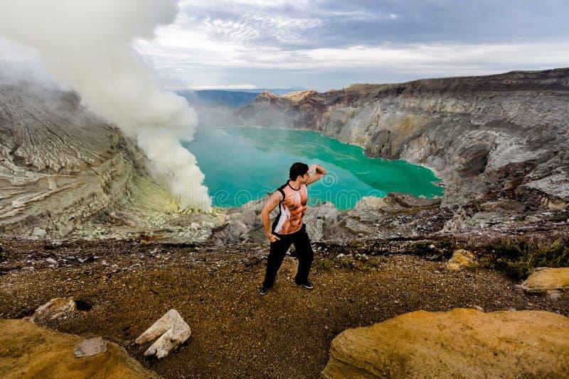 Ung man i krater av en vulkan royaltyfri bild