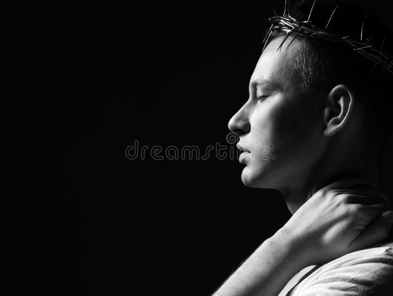 Ung man i krona av taggar, martyren med stängda eys och armen på hans halssidoskott royaltyfri fotografi