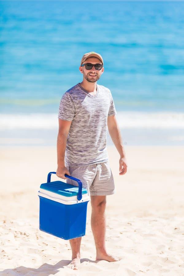 Ung man i kylare för bröstkorg för is för tillfällig sommardräkt bärande med massor av ölflaskor under partiet på sjösidan royaltyfri fotografi