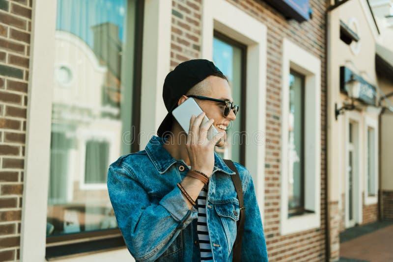 Ung man i lock och solglasögon som talar på smartphonen och bort ser royaltyfria bilder