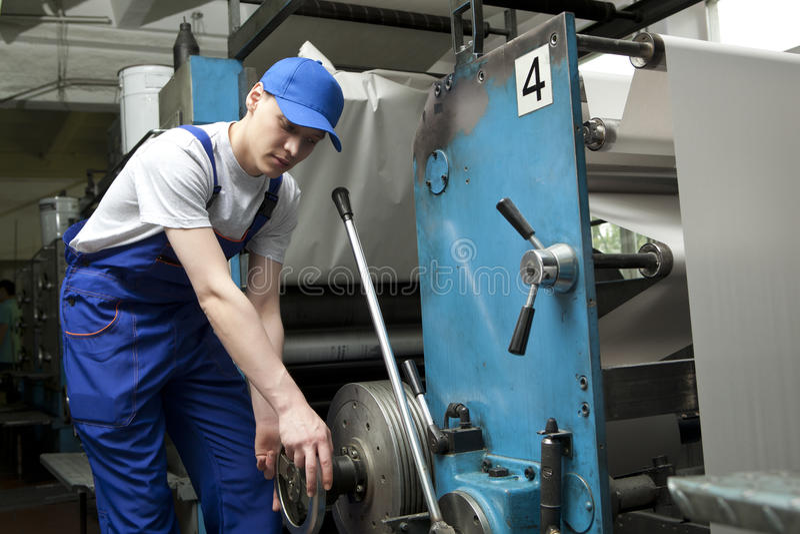 Ung man i locket som arbetar på maskinen för offset- printing royaltyfria foton