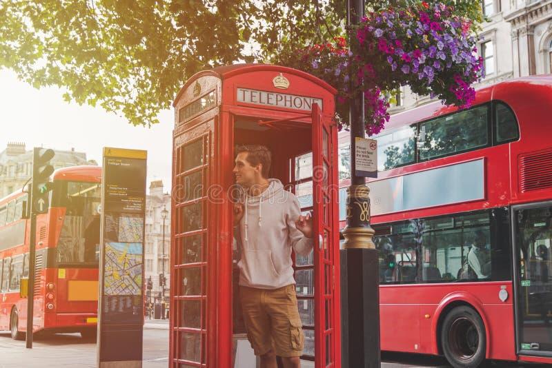Ung man i London som ut ser från ett telefonbås med röda bussar i baksidan royaltyfri foto