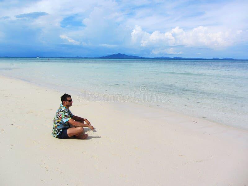 Ung man i meditation nära havet royaltyfri fotografi