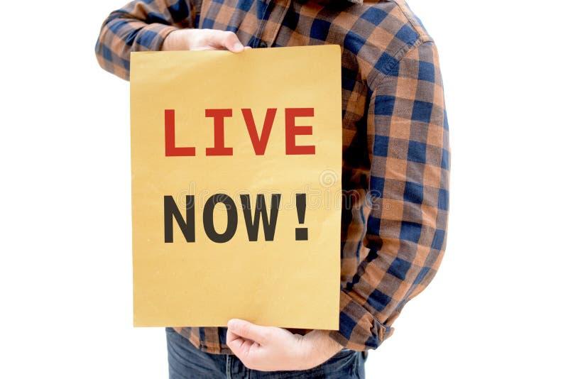 Ung man i plädskjortan som rymmer ett plakat med text: DIREKT NU! arkivfoton