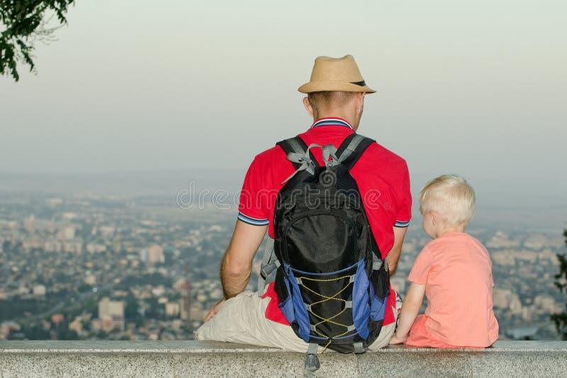 Ung man i ryggsäck- och hattsammanträde med sonen på en bakgrund av en längst ner storstad tillbaka sikt royaltyfria foton