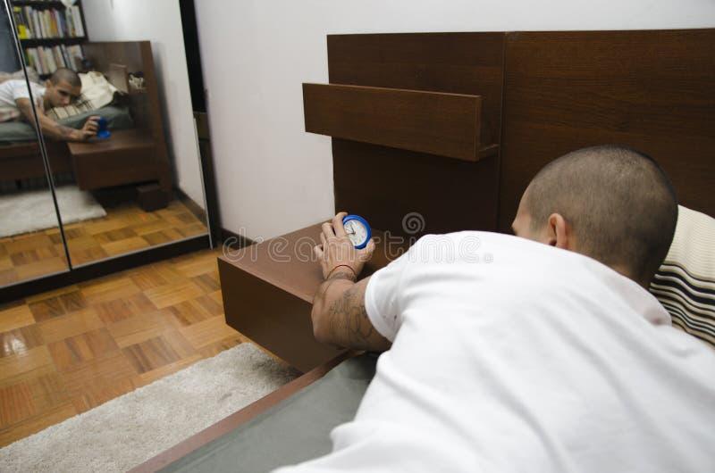 Ung man i säng som vaknar upp, roterande av ringklockan arkivbilder