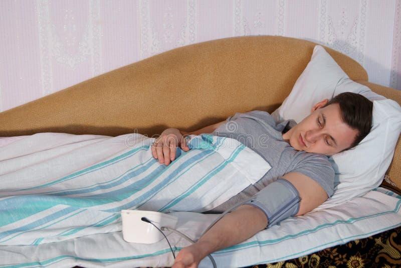 Ung man i sängmåtttryck vid en elektronisk tonometer arkivbild