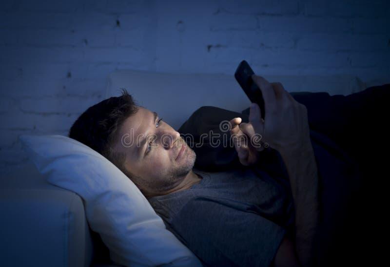 Ung man i sängsoffa hemma sent på natten som smsar på mobiltelefonen i kopplat av lågt ljus royaltyfri bild